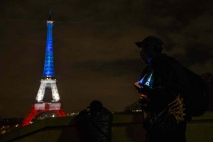 A man selling Eiffel Tower souvenirs looks at the Eiffel Tower illuminated in the French colors in honor of the victims of the attacks on Friday in Paris, Monday, Nov. 16, 2015. France is urging its European partners to move swiftly to boost intelligence sharing, fight arms trafficking and terror financing, and strengthen border security in the wake of the Paris attacks.(AP Photo/Daniel Ochoa de Olza)